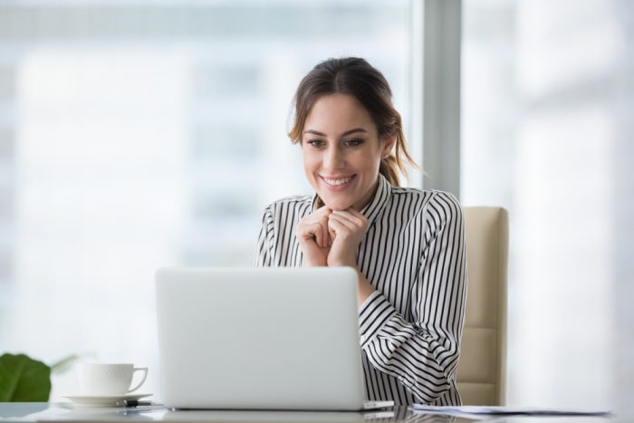 Happy,Smiling,Young,Woman,Looking,At,Laptop,Screen.,Excited,Businesswoman
