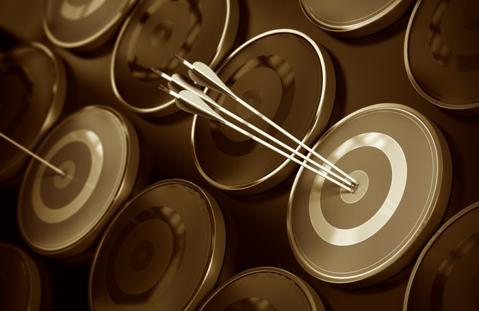 Business excellence, corporate performance management, and achieving goals concept consisting of many targets and three arrows hitting the center of the objective. Depth of field effect.
